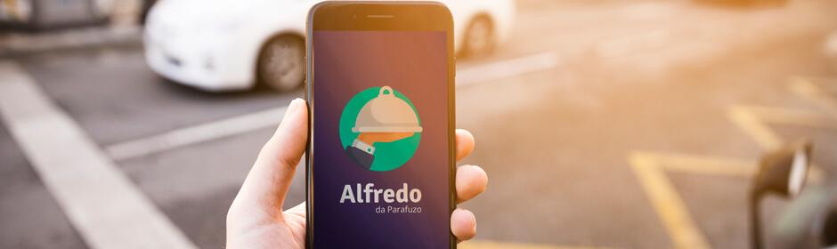 Imagem de uma mão segurando um celular que exibe na tela, a o logo do Alfredo.
