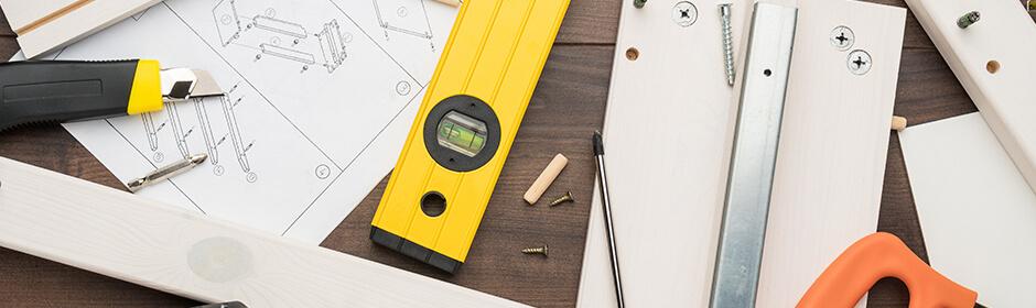 Imagem de ferramentas e objetos relacionados à montagem de móveis em cima de uma mesa de madeira.