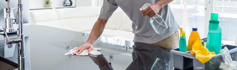Imagem que mostra foca nas mãos de um homem que está limpando a pia, com produtod de limpeza ao seu lado.