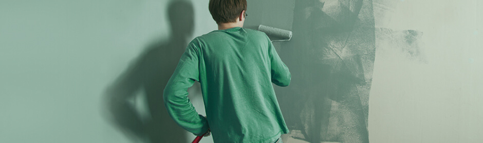 Imagem de homem de costas pintando uma parede